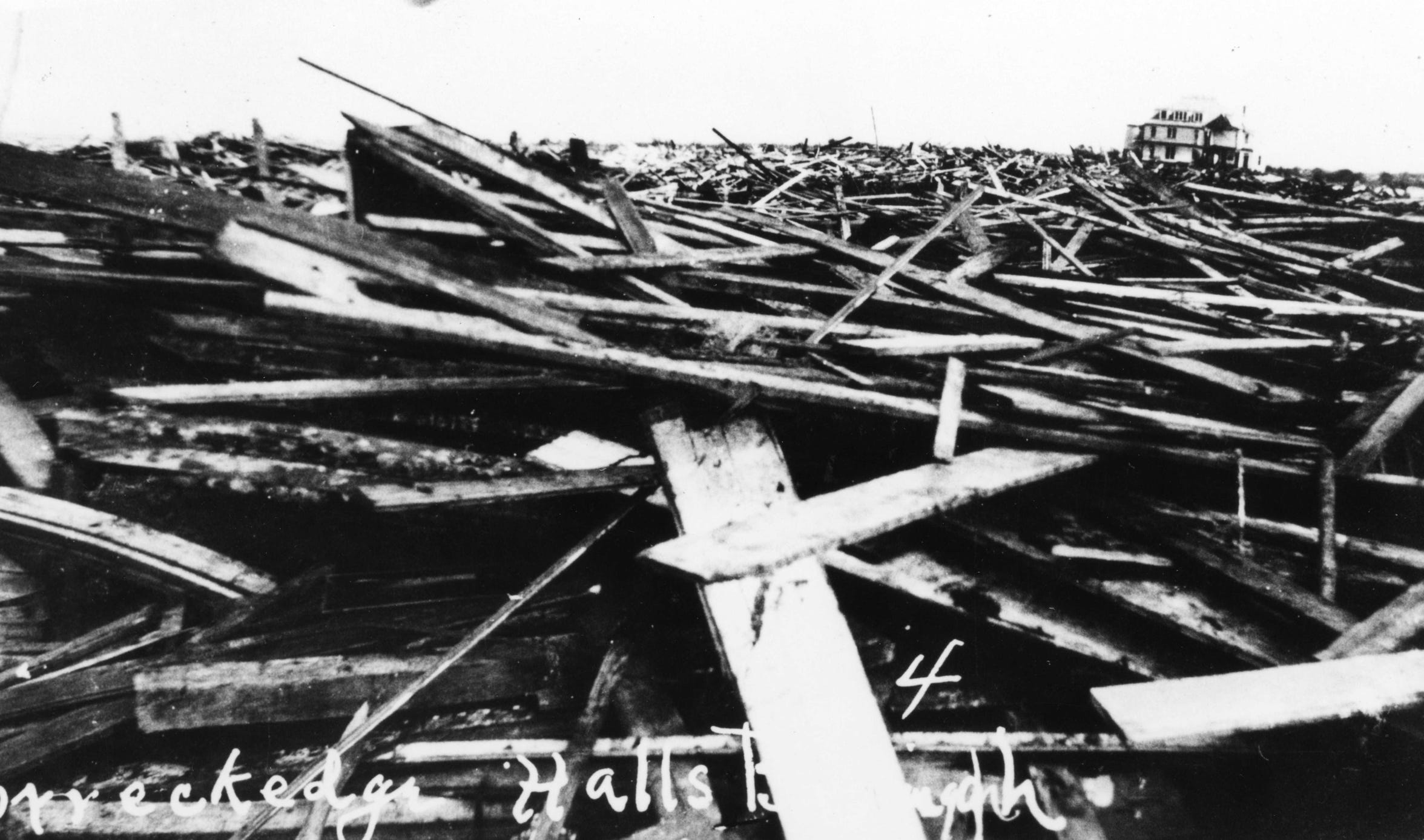 """The wreckage from the 1919 hurricane was piled at the edge of Hall's Bayou. In the distance is Spohn Sanitarium on North Beach. Hall's Bayou was eventually dredged to create the entrance to the Port of Corpus Christi. Photo from """"1919: The Storm - A Narrative and Photographic History"""" by Murphy Givens and Jim Moloney and provided courtesy of the authors."""