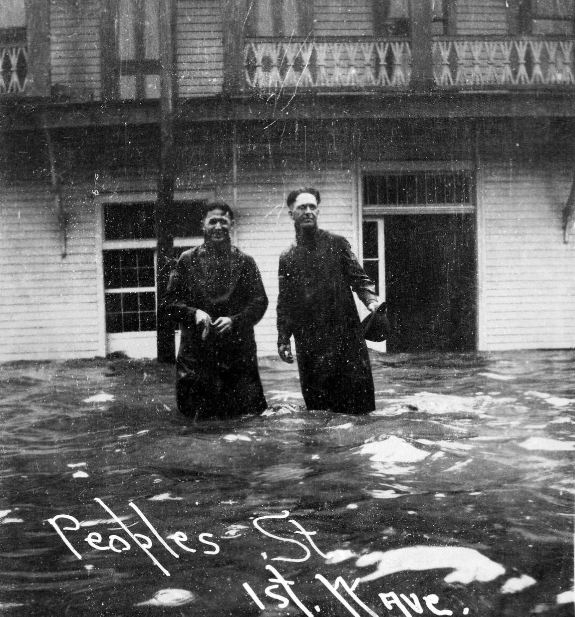 """Two men wade onto Peoples Street as water begins to push into the streets as the 1919 hurricane approached. The storm surge reached 12 feet in downtown Corpus Christi, with high water marks up to 16 feet.Photo from """"1919: The Storm - A Narrative and Photographic History"""" by Murphy Givens and Jim Moloney and provided courtesy of the authors."""