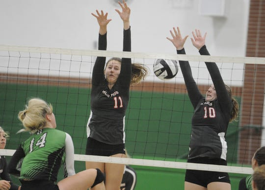 Westfall's Marissa Mullins and Claire Latham attempt to block a ball during a 3-2 win over Huntington at Huntington High School in Chillicothe, Ohio on Tuesday Sept. 10, 2019.