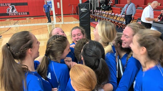 Players celebrate with Villa Madonna Academy volleyball coach Sandi Kitchen after her 400th win Sept. 10, 2019.