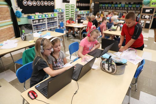 Adalynn Kyly, left, Brie Craycraft, Brooklyn D'Ostroph and Trae Darr work in a first-grade classroom at Warsaw Elementary School recently.