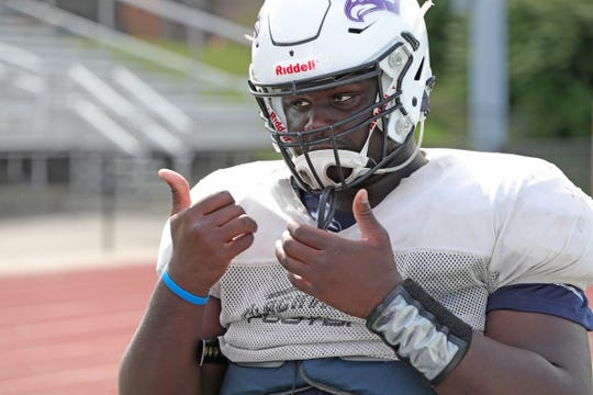 Bloomfield Hills defensive lineman Devin Holmes, who is deaf, signs during practice on Wednesday, Sept. 4, 2019, at Bloomfield Hills High School.