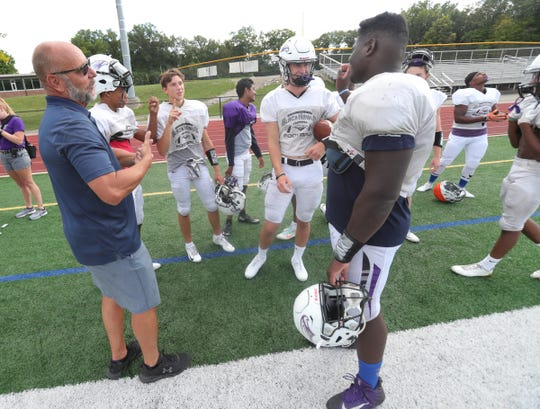 (From left) Interpreter Al Kettinger, Norman Johnson, Dean Bolton and Tasnner Slazinski sign with Bloomfield Hills defensive lineman Devin Holmes, who is deaf, during practice on Wednesday, Sept. 4, 2019, at Bloomfield Hills High School.