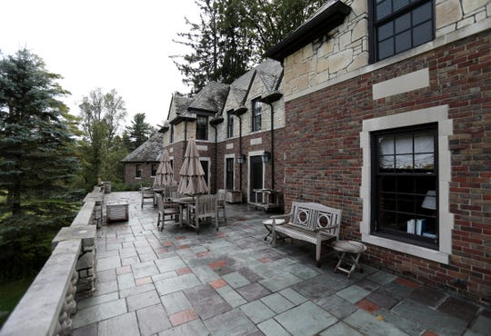 A stone veranda about 70 feet long with a stone railing faces into the 37-acre grounds that are rich with water birds, including sandhill cranes, and other wildlife at the Tudor home in Oakland Township.
