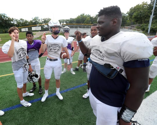 (From left) Bloomfield Hills' Dean Bolton, Santhosh Ramachandran and Tasnner Slazinski sign with Bloomfield Hills defensive lineman Devin Holmes, right, who is deaf, during practice on Wednesday, Sept. 4, 2019, at Bloomfield Hills High School.