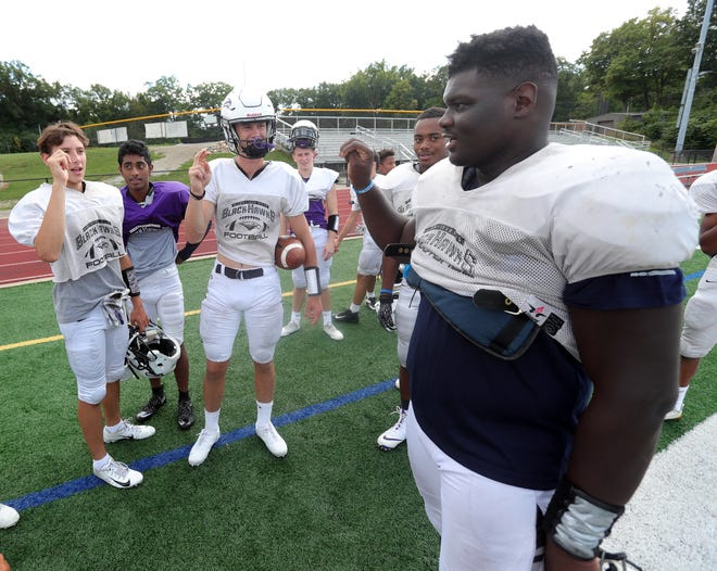 (From left) Bloomfield Hills' Dean Bolton, Santhosh Ramachandran and Tasnner Slazinski sign with defensive lineman Devin Holmes, who is deaf, during practice on Wednesday.