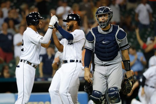 Detroit Tigers' Willi Castro, center, celebrates after scoring the winning run as New York Yankees catcher Gary Sanchez walks to the dugout in the ninth inning against the New York Yankees in Detroit, Tuesday, Sept. 10, 2019.