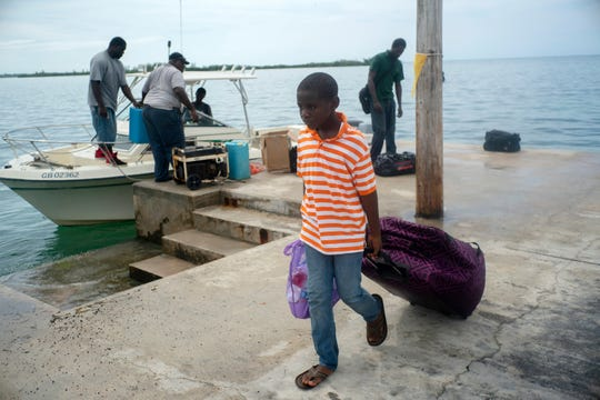 A child evacuated from a nearby Cay due to the danger of floods drags his suitcase when he arrives on a ship at the port before the arrival of Hurricane Dorian in Sweeting's Cay, Grand Bahama, Bahamas, Saturday Aug. 31, 2019.