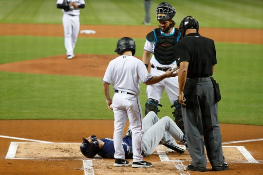 The Milwaukee Brewers' Christian Yelich lies on the ground after fouling a ball off his knee.