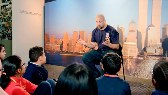 """A New York City Fireman speaking to children in a scene from the documentary """"What Happened on September 11,"""" a short film aimed at young people to explain to them what happened on Sept. 11, 2001. The program debuts on Wednesday."""