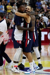 France's Mathias Lessort (left) hugs teammate Evan Fournier as they celebrate defeating the United States on Wednesday during a quarterfinals of the FIBA World Cup in Dongguan in southern China's Guangdong province.
