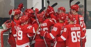 The Red Wings celebrate with goaltender Sean Romeo after defeating the Dallas Stars 6-5 Tuesday in Traverse City to win the prospects tournament.