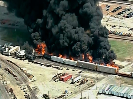 In this image taken from video, rails cars are engulfed in flames after a freight train bearing a flammable liquid used in solvents derailed in Dupo, Ill., a suburb of St. Louis, Tuesday, Sept. 10, 2019. The fire sent thick, black smoke into the air and prompted the evacuation of nearby schools and residences.