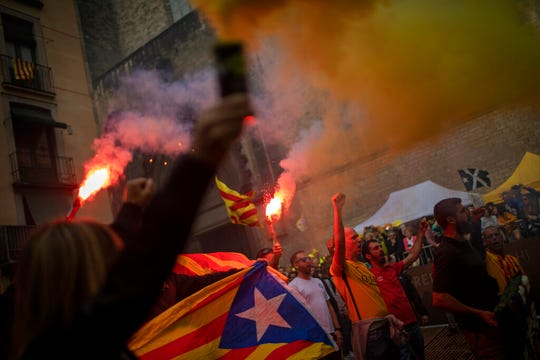 Protesters hold independence flags and flares during the Catalan National Day in Barcelona, Spain, Wednesday, Sept. 11, 2019.