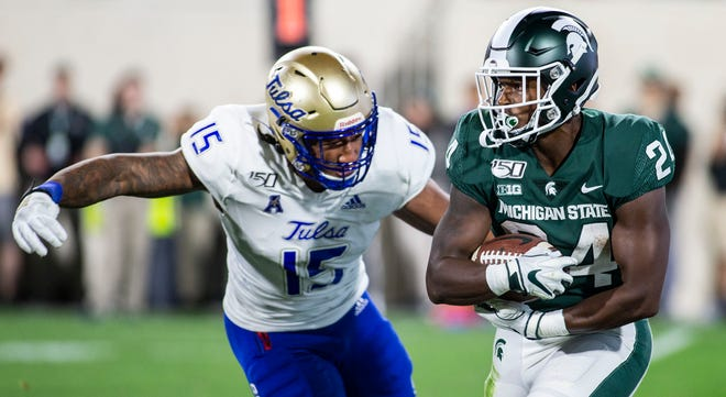 Tulsa defensive end Trevis Gipson, left, attempts a tackle on Michigan State running back Elijah Collins during the second half of an NCAA football game on Friday, Aug. 30, 2019 in East Lansing, Mich. Michigan State won 28-7.
