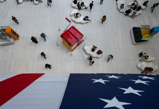 People walk under a flag in the Oculus transportation hub Wednesday, Sept. 11, 2019, in New York. From Europe to Japan, President Donald Trump has stirred up under-the-radar trade disputes that potentially could erupt within weeks or months with damaging consequences.