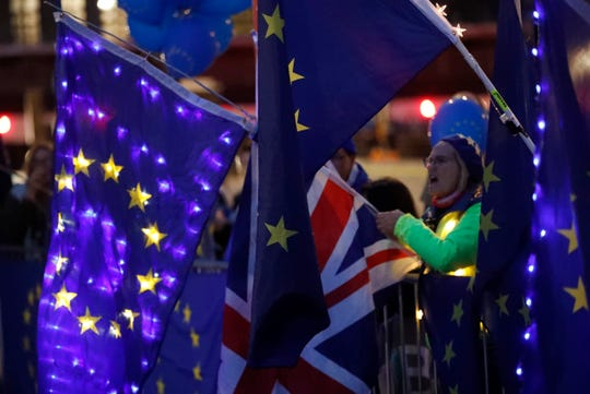 Pro-EU protestors wave flags opposite parliament in London, Monday, Sept. 9, 2019. A Scottish court has ruled that Prime Minister Boris Johnson's decision to suspend the U.K. Parliament was unlawful, but did not order the suspension overturned. Judges said Britain's Supreme Court must make the final decision.
