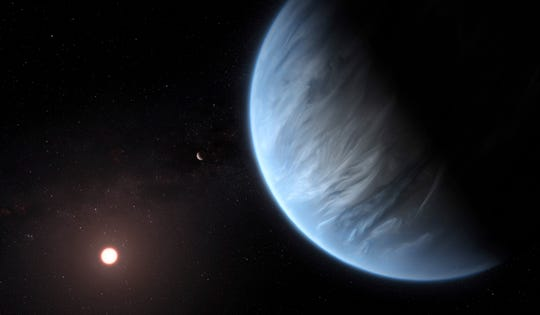 This artist's rendering provided by University College London Centre for Space Exochemistry Data researchers shows Exoplanet K2-18b, foreground, its host star and an accompanying planet in this system.