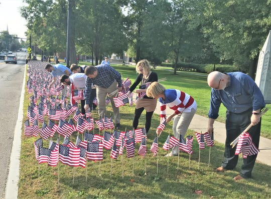 Elmira College faculty members and students place hundreds of American flags along Park Place on Wednesday morning in memory of the victims of the Sept. 11, 2001 terrorist attacks.