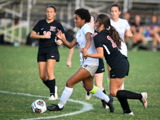 Reitz's Naomi Splittorff (9) pushes the ball past defenders Harrison's Kaily Medina (15) and Payton Tyler (6) as the Reitz Panthers play the Harrison Warriors at the EVSC Soccer Complex Tuesday evening, September 10, 2019.