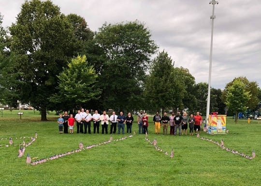 During the 9/11 Never Forget Ceremony, community members placed flags in the ground of the date 9/11 as well as took part in a three-minute moment of silence in remembrance. Pictured are from left: Aaron Bell, Heather Bell, Austin Bell, Fond du Lac Fire Rescue Assistant Chief Troy Haase, Assistant Chief Erick Gerritson, Assistant Chief Todd Janquart, Assistant Chief James Knowles, City Council Member and event organizer Ben Giles, Fond du Lac Fire/Rescue Chief Peter O'Leary, City Council Member Dan Degner, Lisa Chambers Siefert  James Graves, Ellen Wendlandt, Shavana Talbert, Vicente Lezama, Daisy Frazier, Antonio Godfrey, Loree Shady and Zoe Leu. Others who attended included event organizer Bre Zoch, JJ Raflik, Representative Jeremy Thiesfeldt and Father Ryan Pruess.