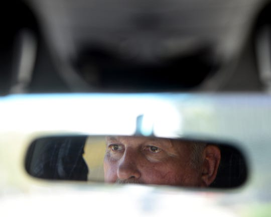 The rearview mirror catches the reflection of Russell Ross in his car as he drives along the route he took Jonelle Matthews home.