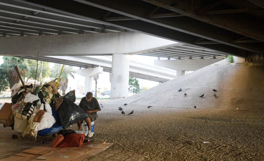 A homeless woman sits with one of her shopping carts under a highway in San Antonio, Texas on Wednesday, Sept. 4, 2019.