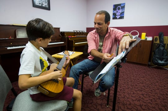 Leland Ballo, 7, of Cape Coral, learns to play the ukulele under the instruction of music teacher Juan Pablo Oliva Tuesday, September 10, 2019. 
