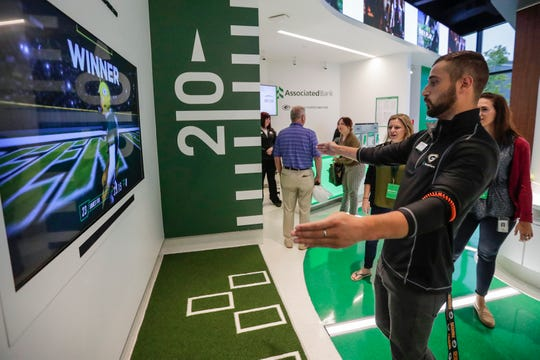 Maxwell Diederich, a banker, shows off his skills against his coworkers on the Train Like a Champion game inside the new interactive Packers-themed Associated Bank branch Wednesday in the Titletown District in Ashwaubenon. Using pressure sensing pads located on the floor, fans will follow on-screen directions to run their fastest practice punt return solo or against another player.