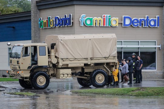 The Green Bay Metro Fire Department evacuates people from Familia Dental due to flooding Wednesday, September 11, 2019, in the 1900 block of Main Street in Green Bay, Wis.