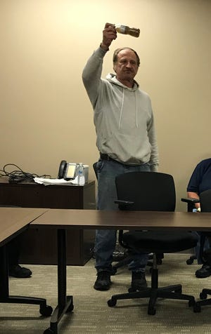 While speaking to the Kewaunee County Land & Water Committee at its Sept. 10 meeting, Joe Musial of the Town of Lincoln holds up a bottle of polluted groundwater he collected near his home during a manure runoff incident four days before.