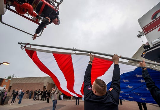 Great Falls Fire Department firefighters prepare to raise a large flag, using ladder trucks, over 1st Avenue South in front of Fire Station 1 at a ceremony honoring those who died in the Sept. 11, 2001 terrorist attacks that killed nearly 3,000 people.