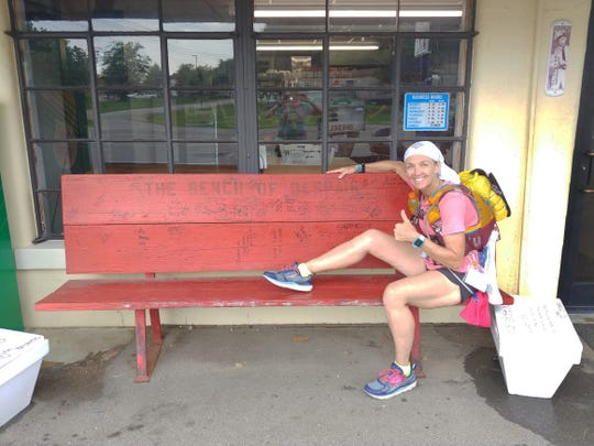 Managing a smile and a thumb's up, Sharon Carver in 2018 poses on the landmark known as The Bench of Despair outside the roadside Glendale Market at about milepoint 185, 128 miles from the finish. It symbolizes a low point that many participants feel at that point in the Last Annual Vol State Run, still so far from the end.