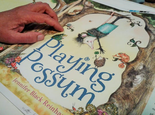 "Proofs for the cover of her upcoming book titled ""Playing Possum"" are examined by author/illustrator Jennifer Black Reinhardt in her studio."