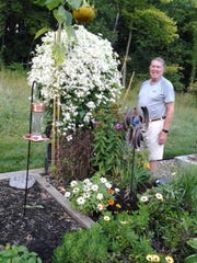 Don Reddel stands next to a beautiful Sweet Autumn clematis in his garden.