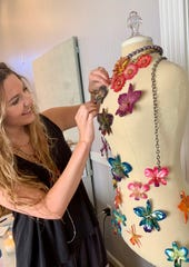 KK Buteau of Madison attaches pins made of preserved blossoms to a mannequin in her studio.