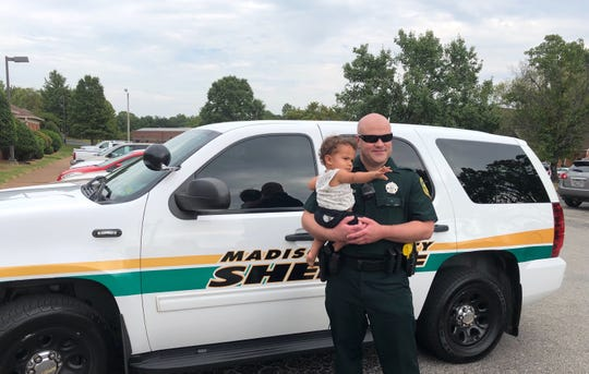 Madison County Sheriff's Deputy Brandon Massey holds a child he saved from choking at Madison County Sheriff's Office in Denmark, Tenn.