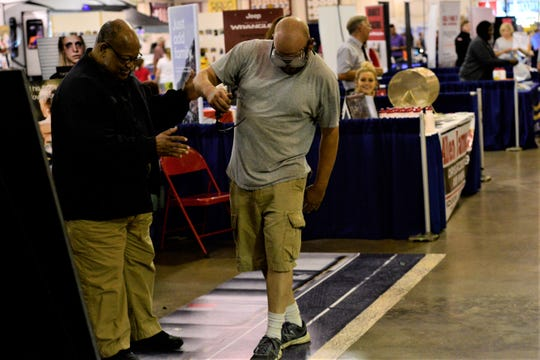 Brandon Dittaugh, right, is assisted by Madison County Sheriff's Office Specialist Abe Jones, left, as he tries out the drunk goggles at the West Tennessee State Fair on Sept. 10, 2019 in Jackson, Tenn.