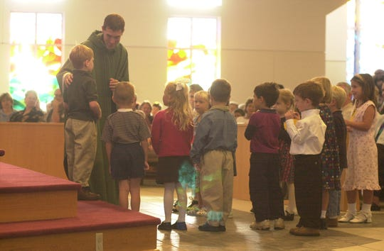 "Rev. Ragan Schriver of All Saints Catholic Church asks the youngsters if  they had any special prayers on during the 8:30 a.m. mass on Sunday, Sept. 16, 2001. ""What we have to see in this disaster is to love each other and help each other.  This week we've been searching for God in a faraway place, but he is right there beside those people suffering,""  said Schriver."