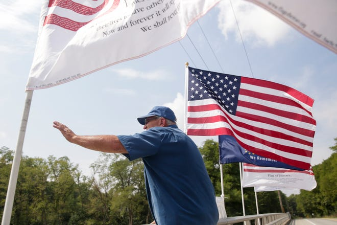 Robert McKinnis waves to honking motorists from E 200 N above I-65, Wednesday, Sept. 11, 2019 in Lafayette. McKinnis has spent the last 8 anniversaries of 9/11 on the bridge waving to passing motorists from between his American flags.