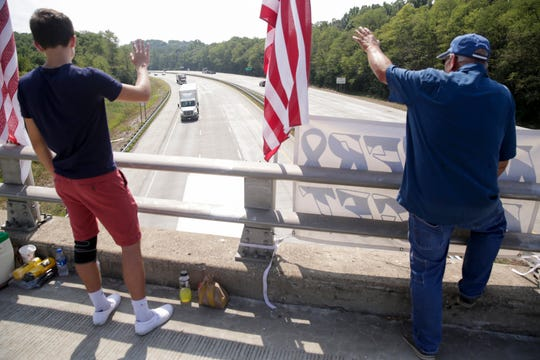Robert McKinnis, right and his grandson, Gavin Van Deventer, 17, wave to honking motorists as they stand on E 200 N above I-65, Wednesday, Sept. 11, 2019 in Lafayette. McKinnis has spent the last 8 anniversaries of 9/11 on the bridge waving to passing motorists from between his American flags.
