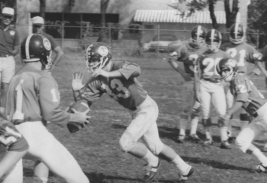 Trinity's offensive star Alan Hennessey, shown taking a handoff from quarterback Dennis Scully in yesterday's workout. Hennessey, a senior, has scored four touchdowns for Trinity. By Warren Klosterman, The Courier-Journal. Sept. 19, 1968