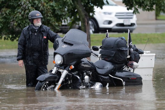 A man stands stranded with his motorcycle as he waits for the Green Bay Fire Department to tow his bike from the middle of the 1900 block of Main Street on Wednesday.
