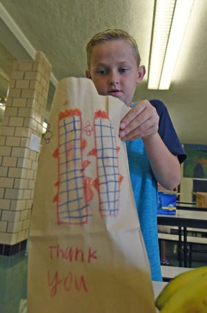 Central Elementary fourth grader Austin Brokaw packages a lunch Wednesday morning for first responders on the 18th anniversary of the 9/11 terrorist attacks.