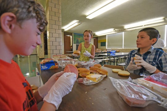 Trevor Reed, Ashton Williams and Ashton Boggs, all fourth graders at Central Elementary in Lexington, make sandwiches Wednesday morning for first responders.