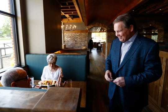 Tommy Peters greets customers during a soft opening at the Moondance Grill in Germantown.