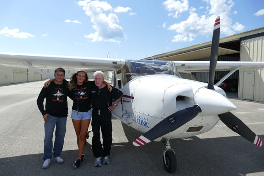 Flight instructor Andrés Gutiérrez, pilot Andi Miller and veterinarian David C. Randall stand next to the Cessna 182 at Naples Airport on Sept. 10, 2019.