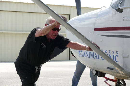 David C. Randall, second-generation veterinarian and owner of Big Cypress Animal Clinic, helps pushing the Cessna 182 inside a hangar at Naples Airport on Sept. 10, 2019.