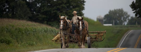 An Amish teen pulls farm machinery down a road in La Farge.