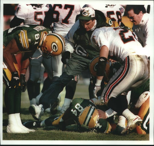 Green Bay trainer Pepper Burruss rushes to Sterling Sharpe's aid, while Anthony Morgan (left) and Atlanta's Brad Edwards watch December 18 at County Stadium. The play provided the first evidence of a career-threatening neck injury that ended Sharpe's season.